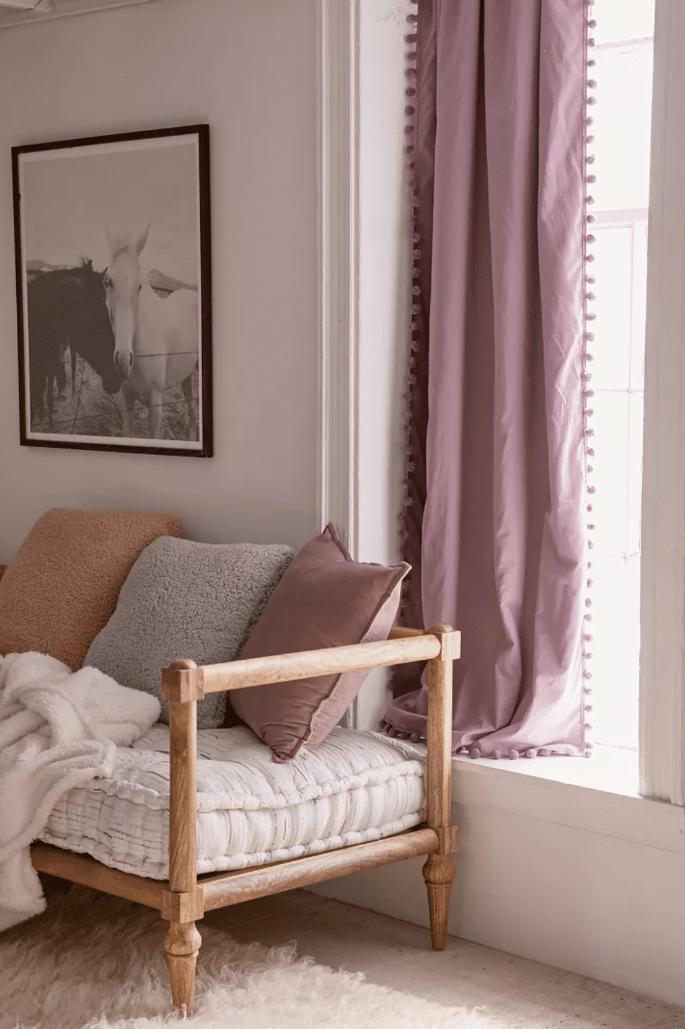 A lavender curtain lined with pom-poms, which is currently for sale at Urban Outfitters