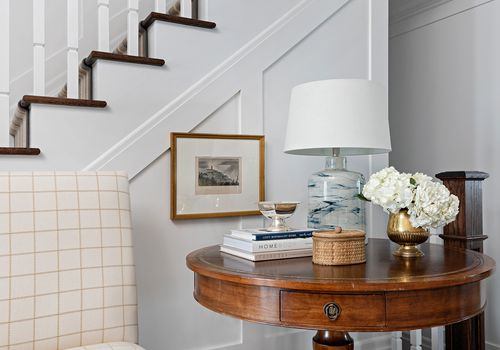 how to decorate sustainably- entryway with slipcovered chair and vintage table
