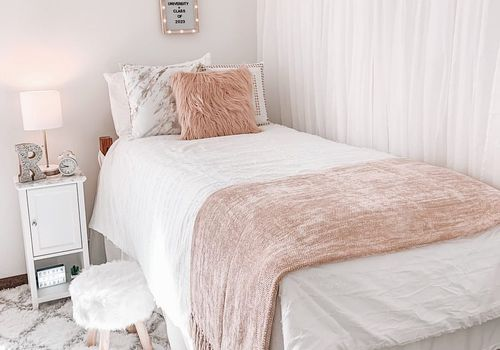 Light pink dorm room bed.