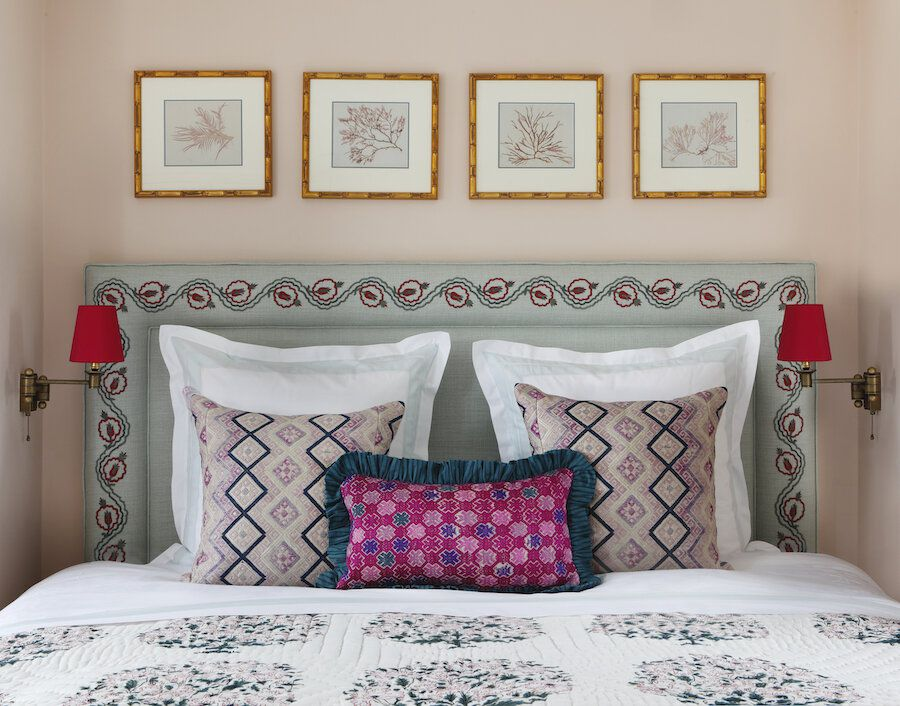 A bedroom with light pink walls, printed lavender walls, and a printed mint headboard