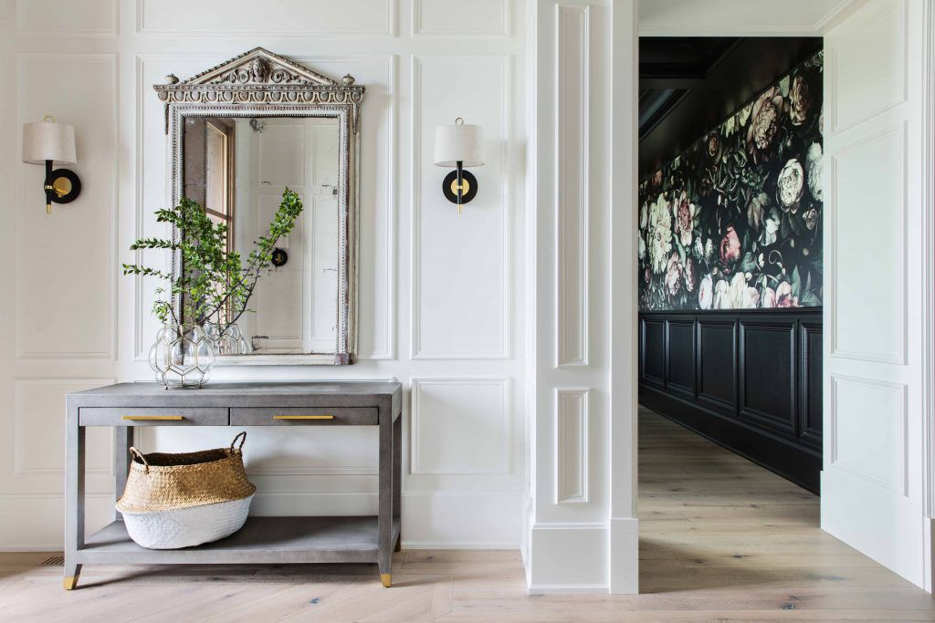 An ornate metal mirror over a console table, next to a wallpaper-lined hallway