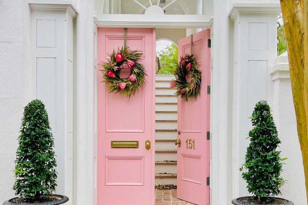 Front door exterior with pink door and wreath.