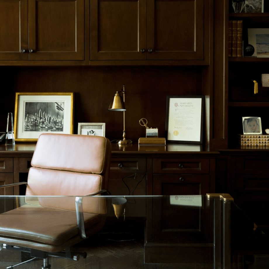 A wood-filled home office with streamlined brass and silver finishes