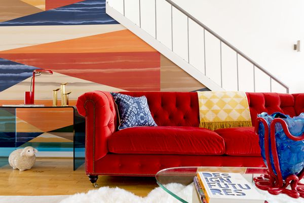Bright crimson sofa in front of bold wallpapered staircase.
