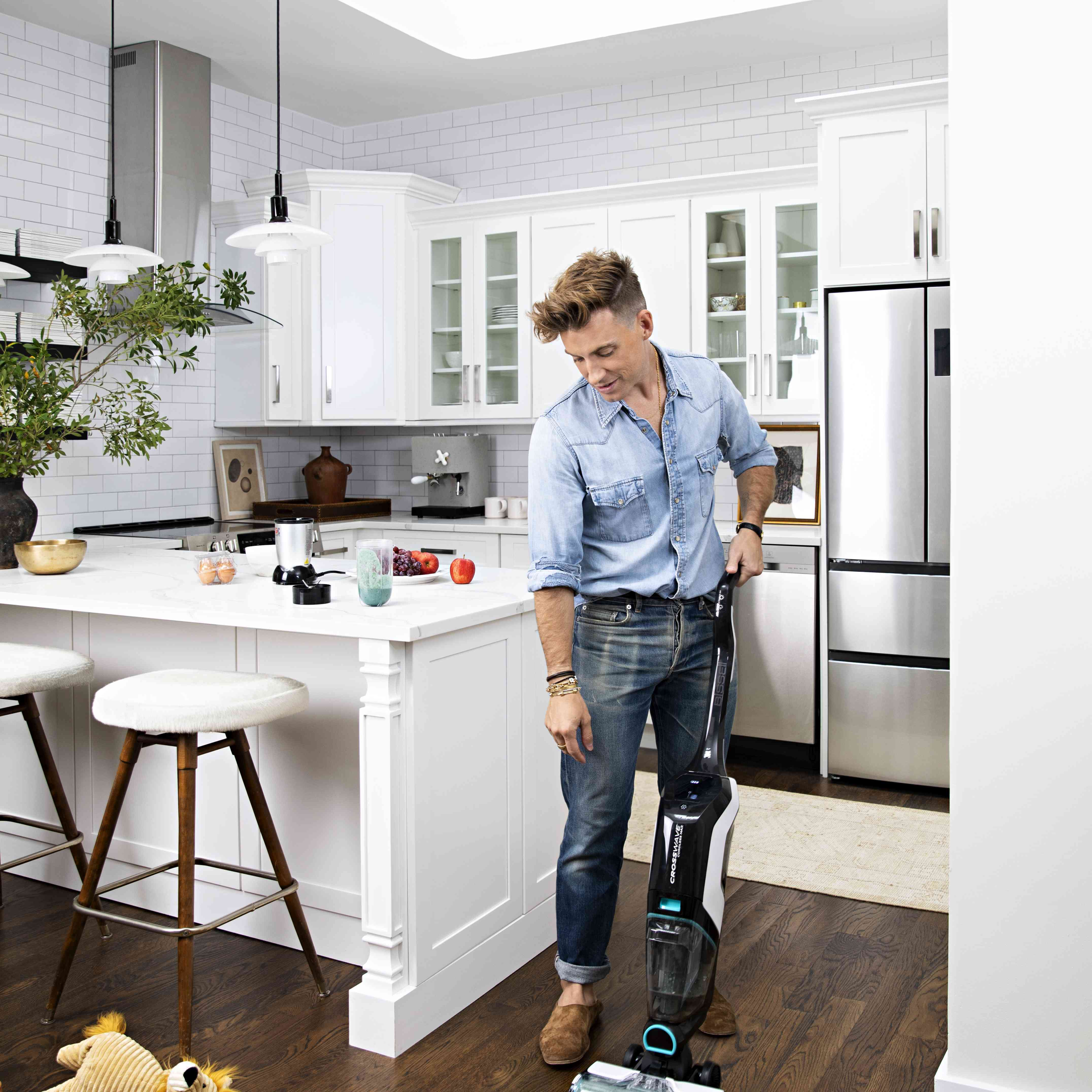Jeremiah Brent using BISSELL CrossWave Cordless Max to clean a spill in his NYC kitchen