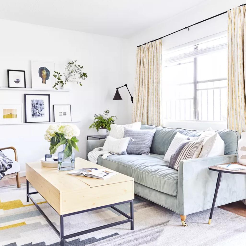 Sala de estar de estilo con alfombra estampada geométrica y mesa de centro de madera de abedul
