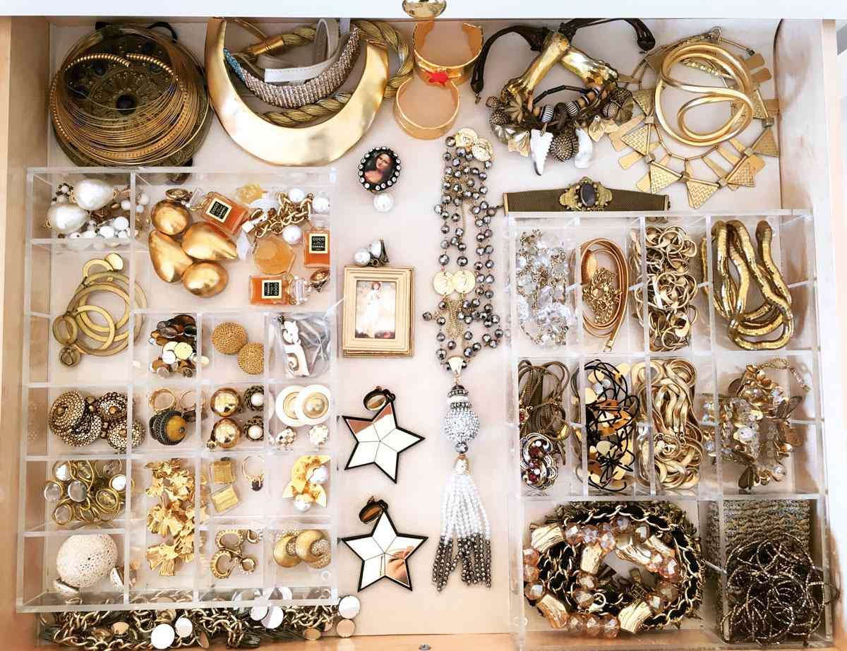 Gold jewelry in organizer bins.