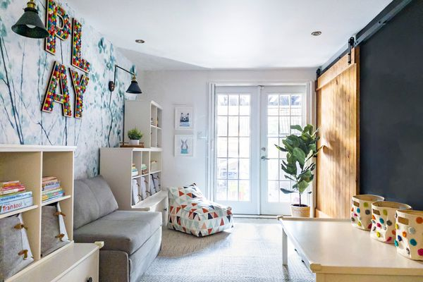 Playful and bright nursery with sliding wood door.