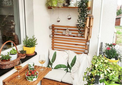balcony with small folding table, floating shelves and plants