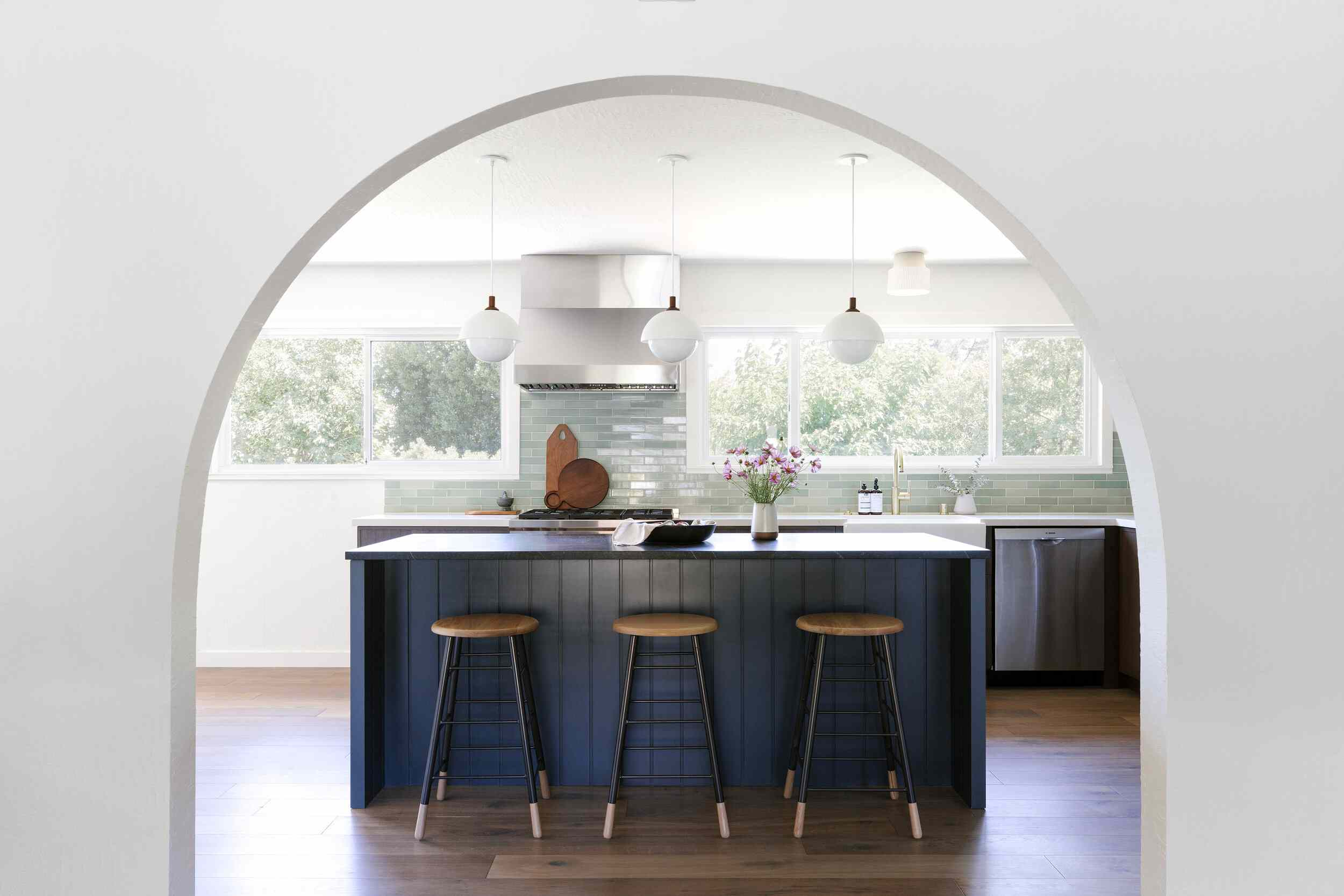 A kitchen with a dark blue island and a light blue backsplash