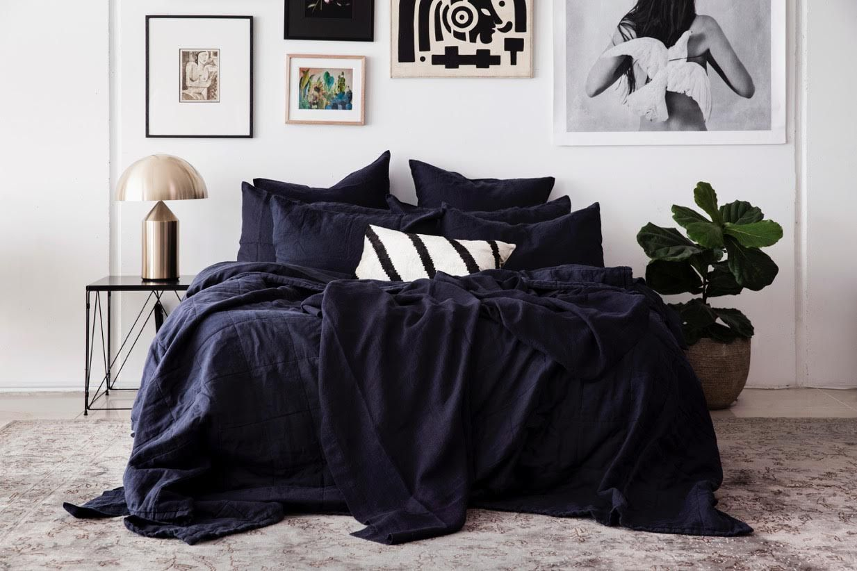 A luxurious bed dressed in draped black bedding.