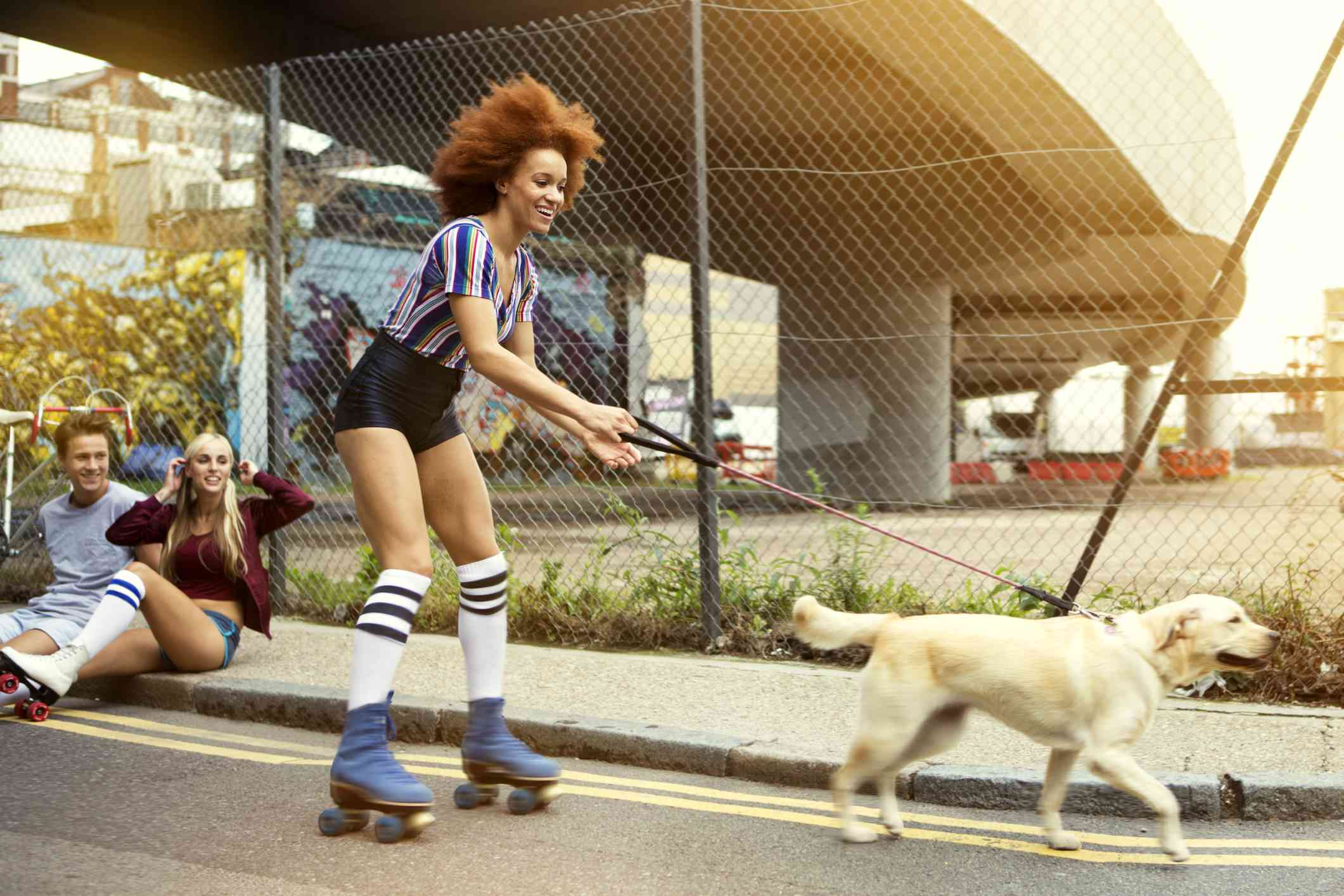 Young woman rollerskating with dog