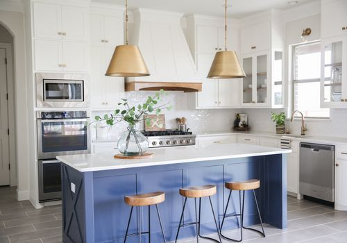 White kitchen with blue island and gold pendant lights.