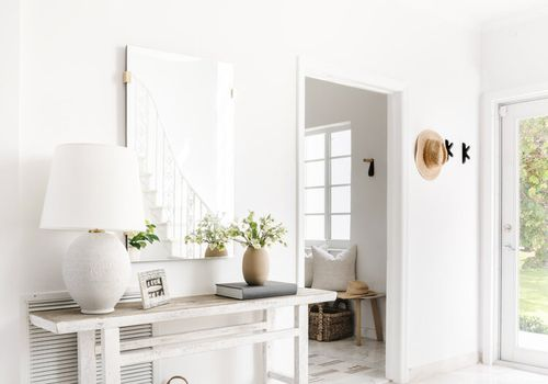 Bright and sunny white entryway with mirror and woven rug.