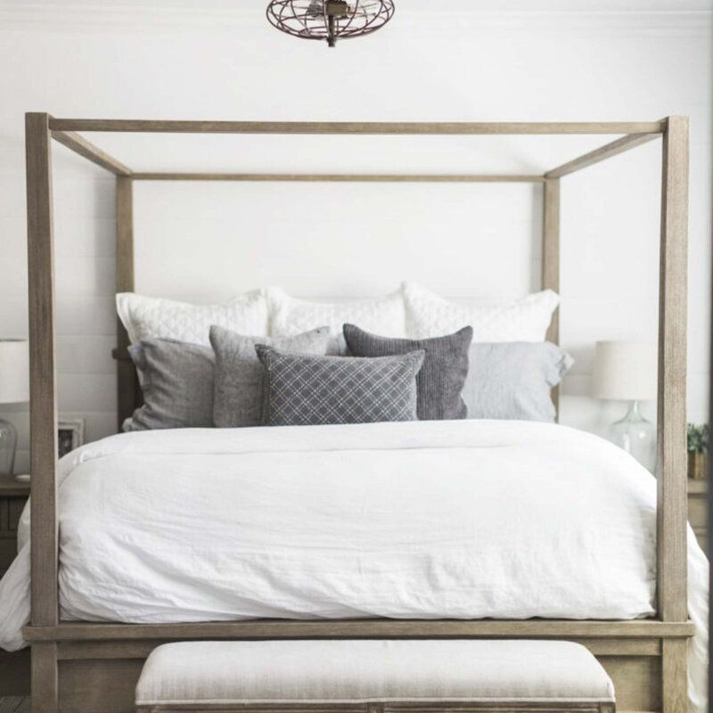 A bedroom white a wood canopy bed and an industrial fan