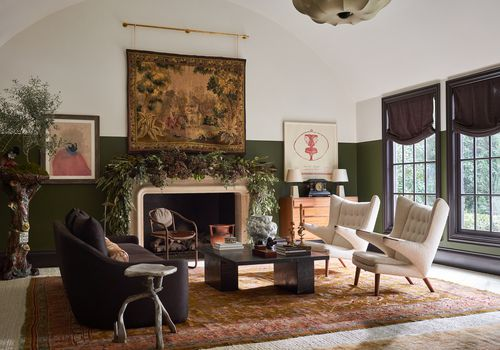 Overview of this ornate living room with greenery and vintage tapestry.