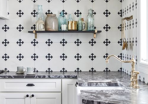 A kitchen with a black and white tiled backsplash and striking marble countertops