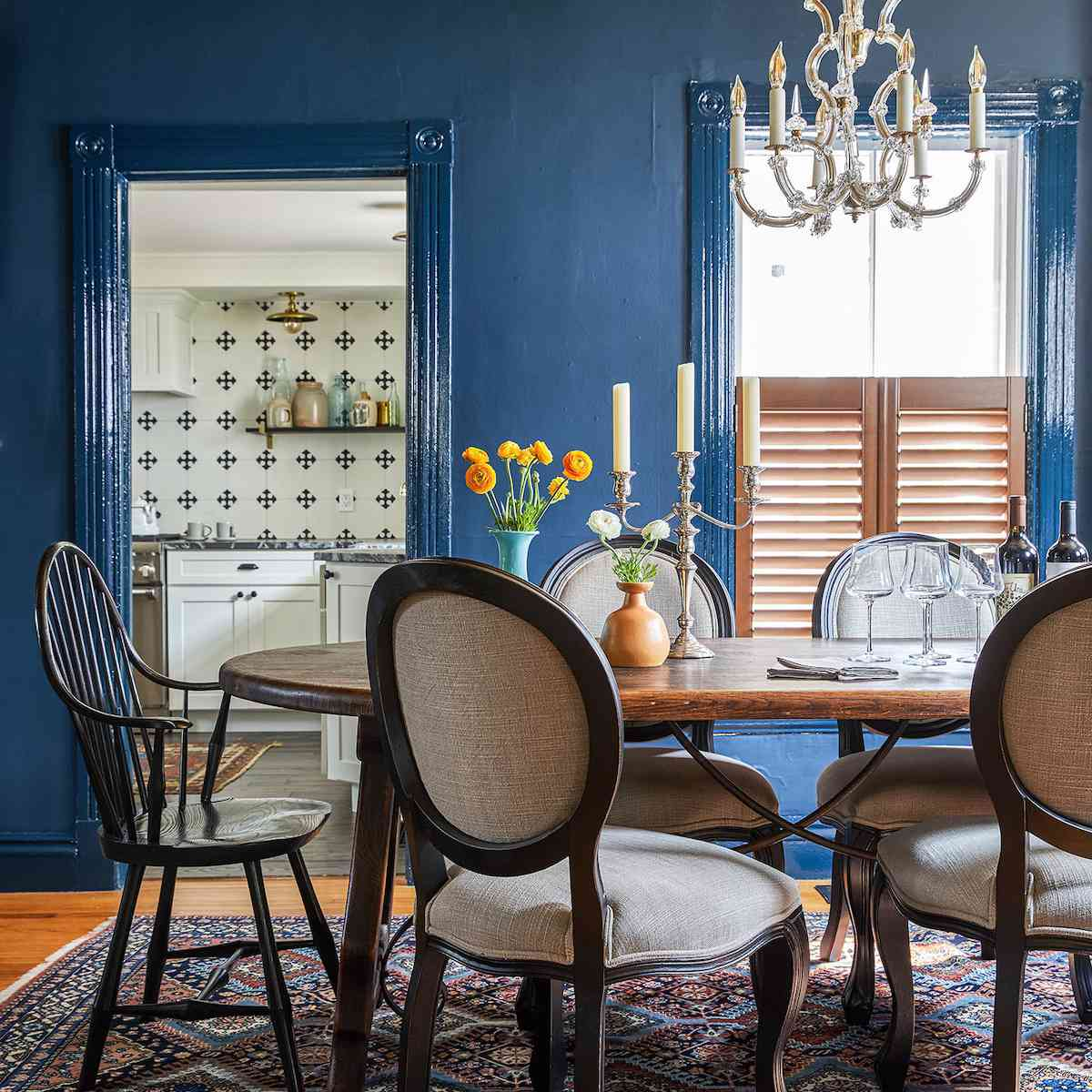 A dining room with dark blue walls and a copper statement ceiling