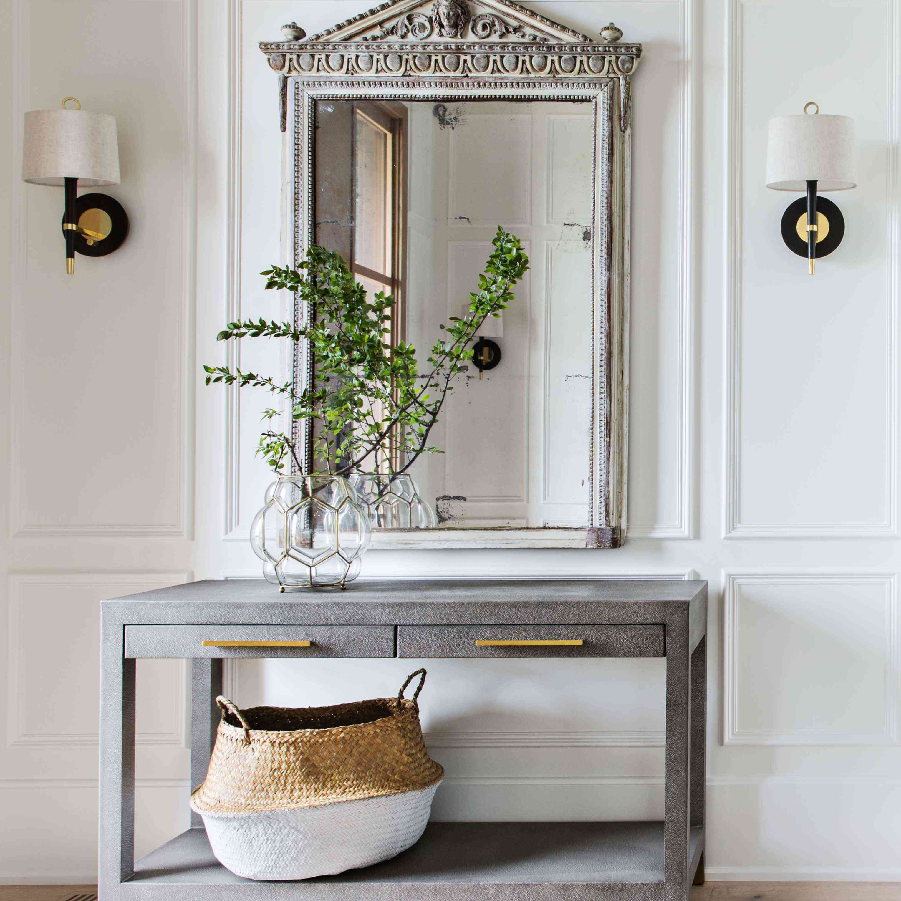 Mirror hangs above console in foyer