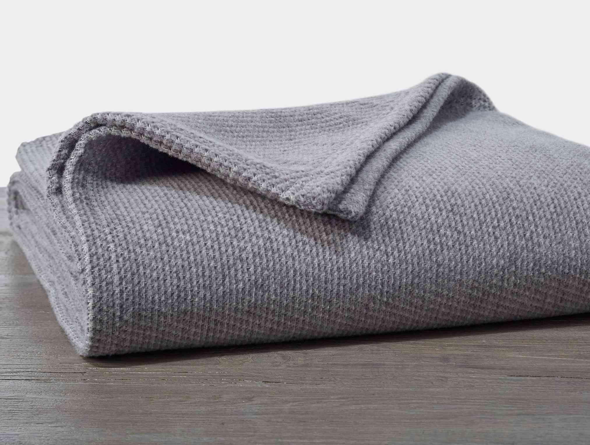 A folded gray cotton-wool blend blanket.