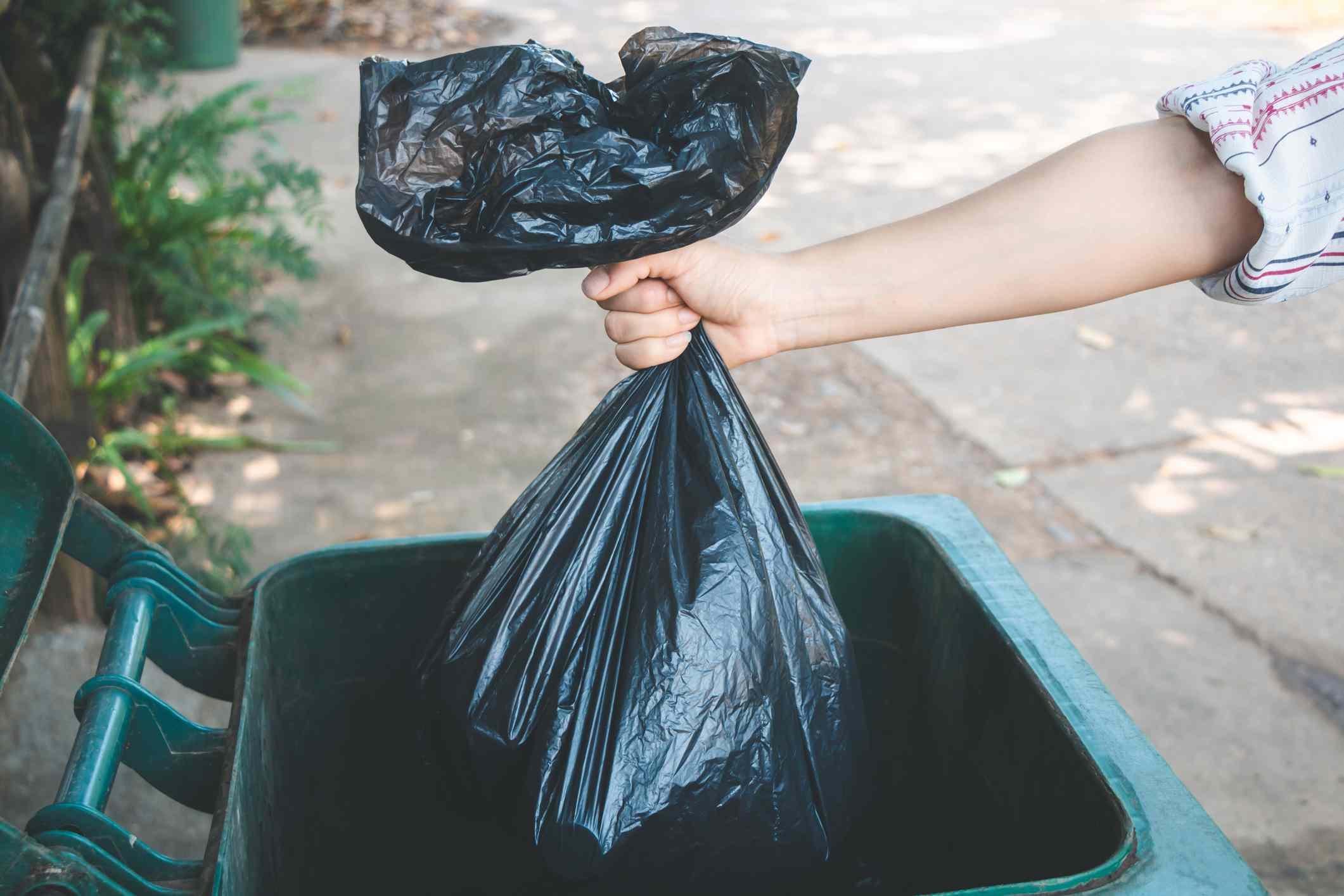 Arm disposes of garbage bag