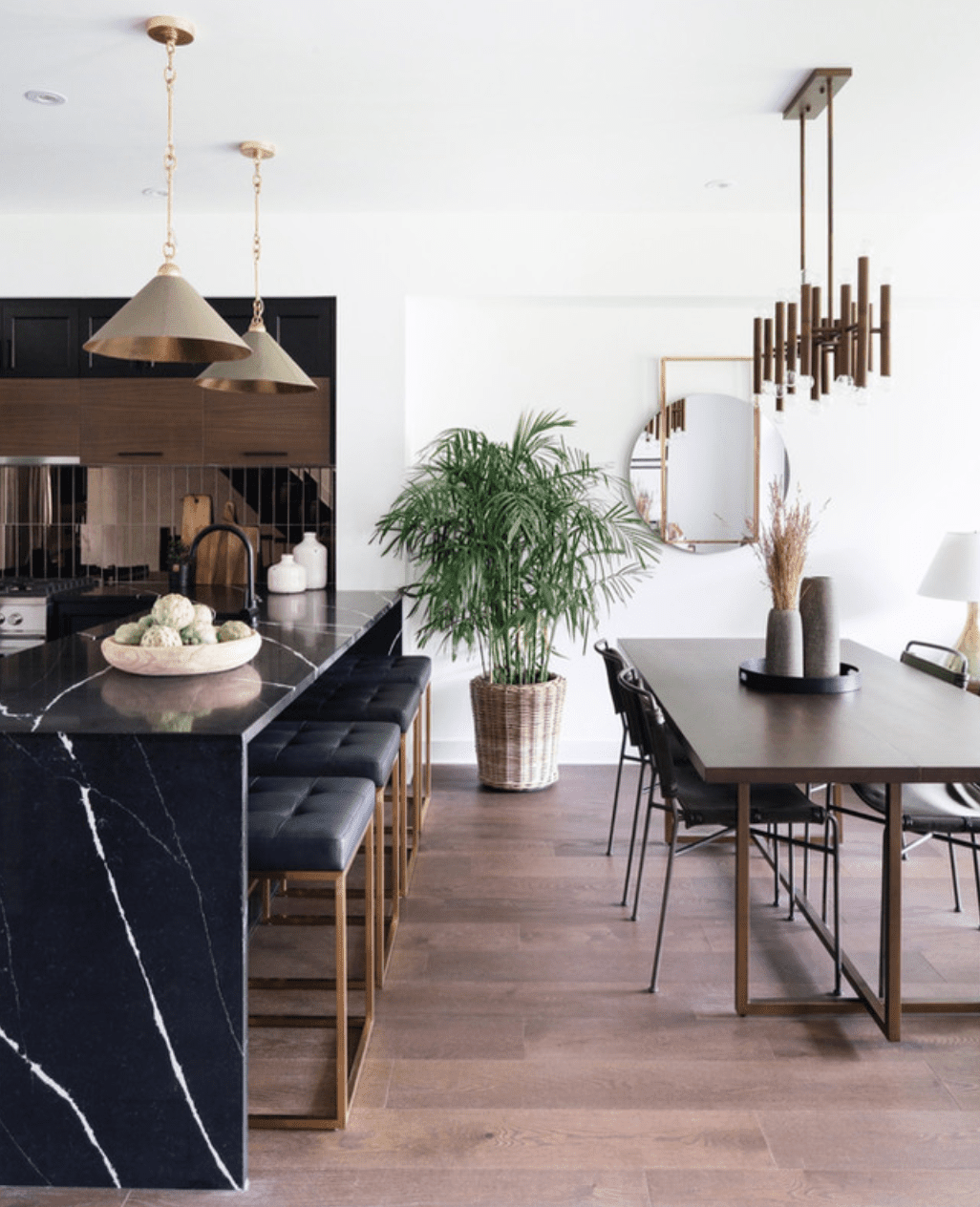 A kitchen with sleek marble countertops and a very shiny gold backsplash