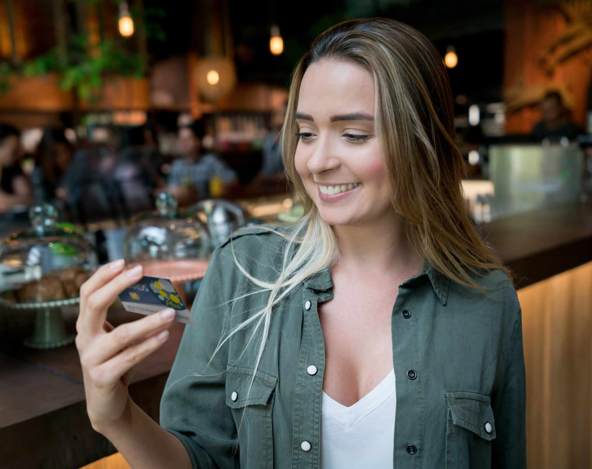 Woman holds up gift card in restaurant