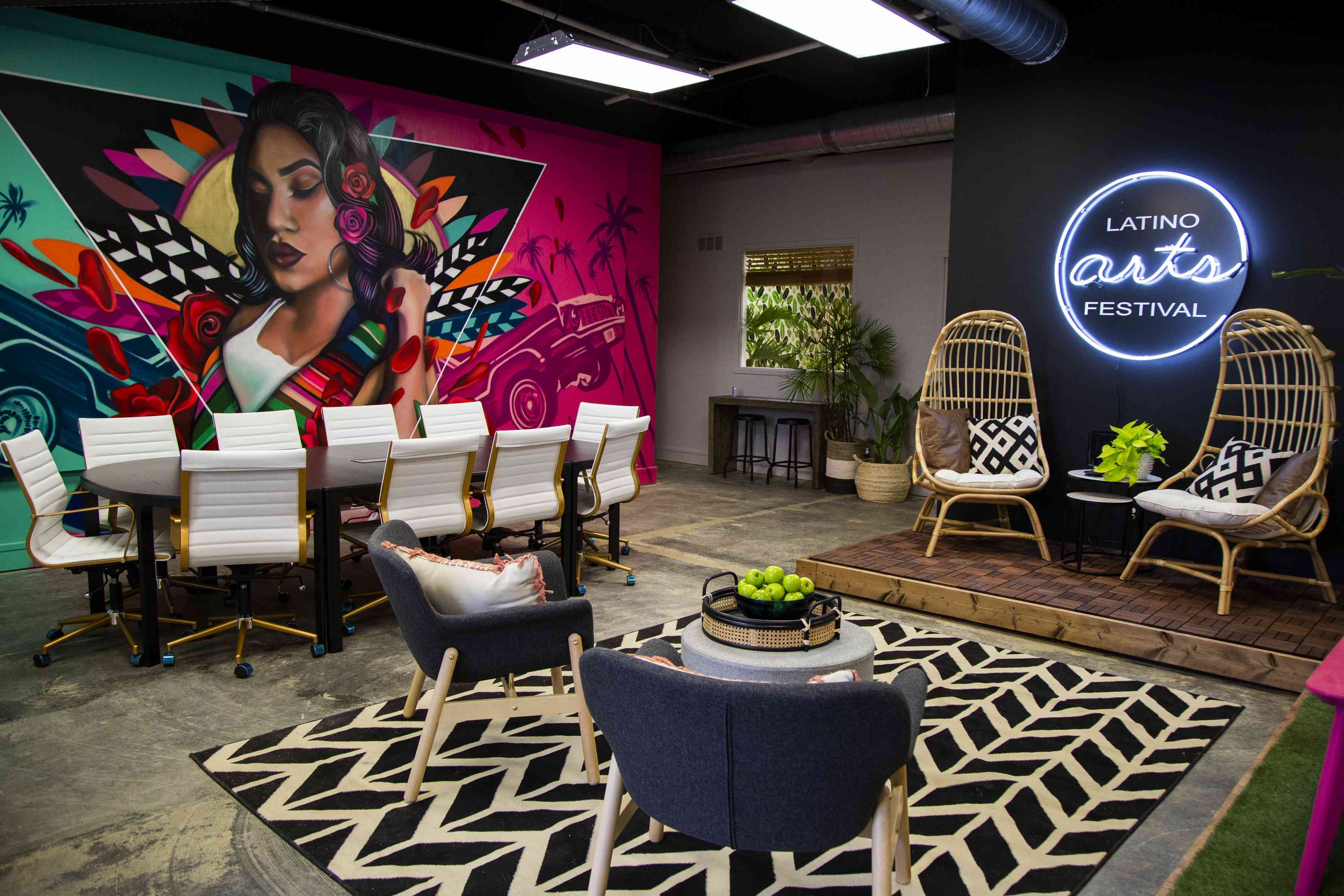 Office with large mural, a neon sign, and multiple seating options