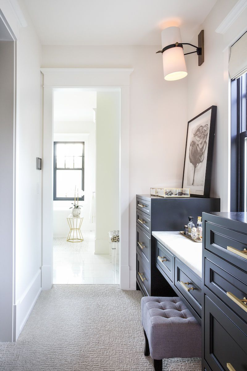 Walk through closet with navy cabinets, jewelry boxes, and a perfume tray