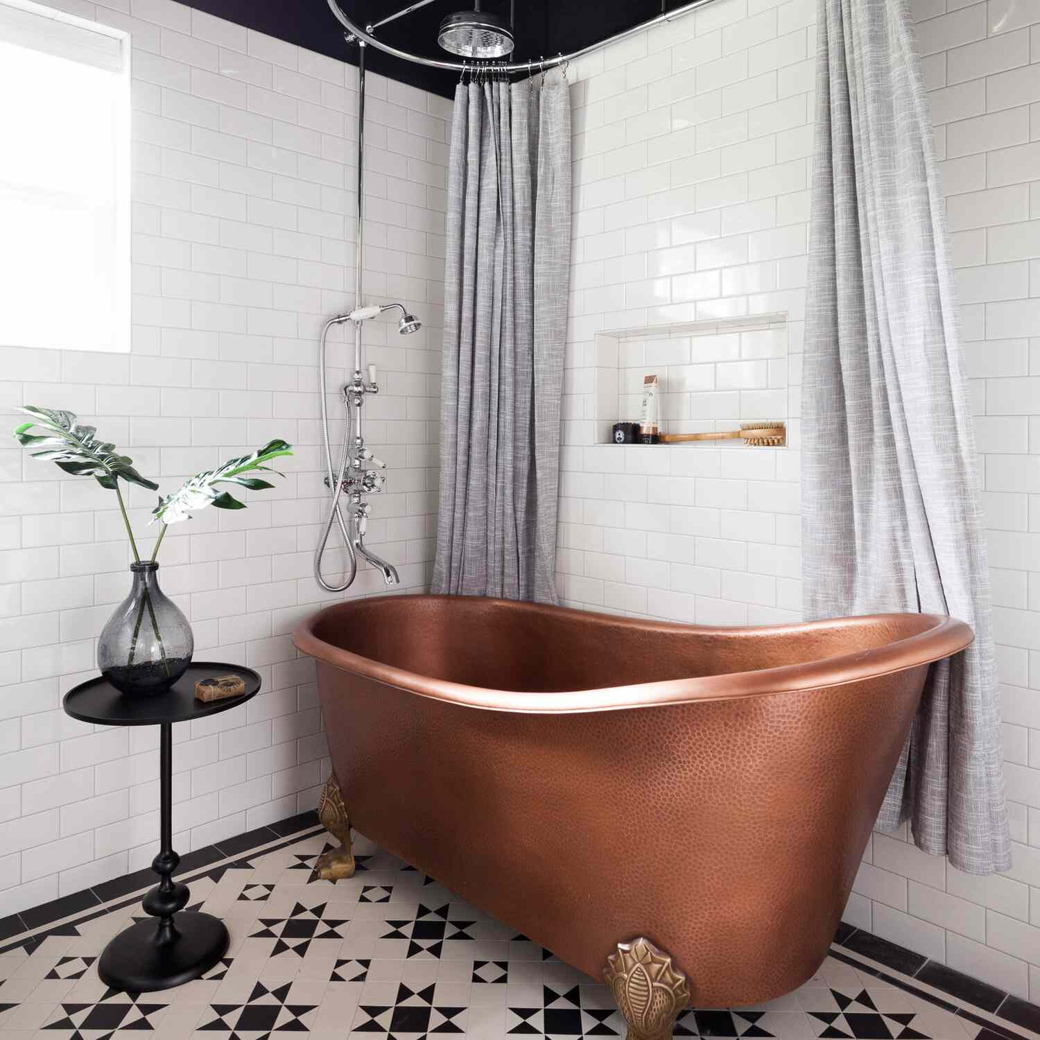 A bathroom with a rose gold clawfoot tub and a gray shower curtain