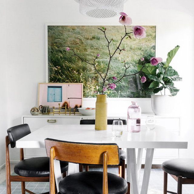 Dining room with black and white furniture and green art