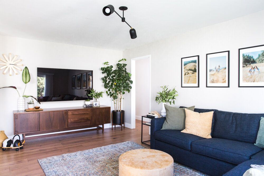 Spacious living room with plants and TV mounted on the wall.