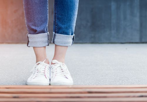 woman wearing white tennis shoes and jeans