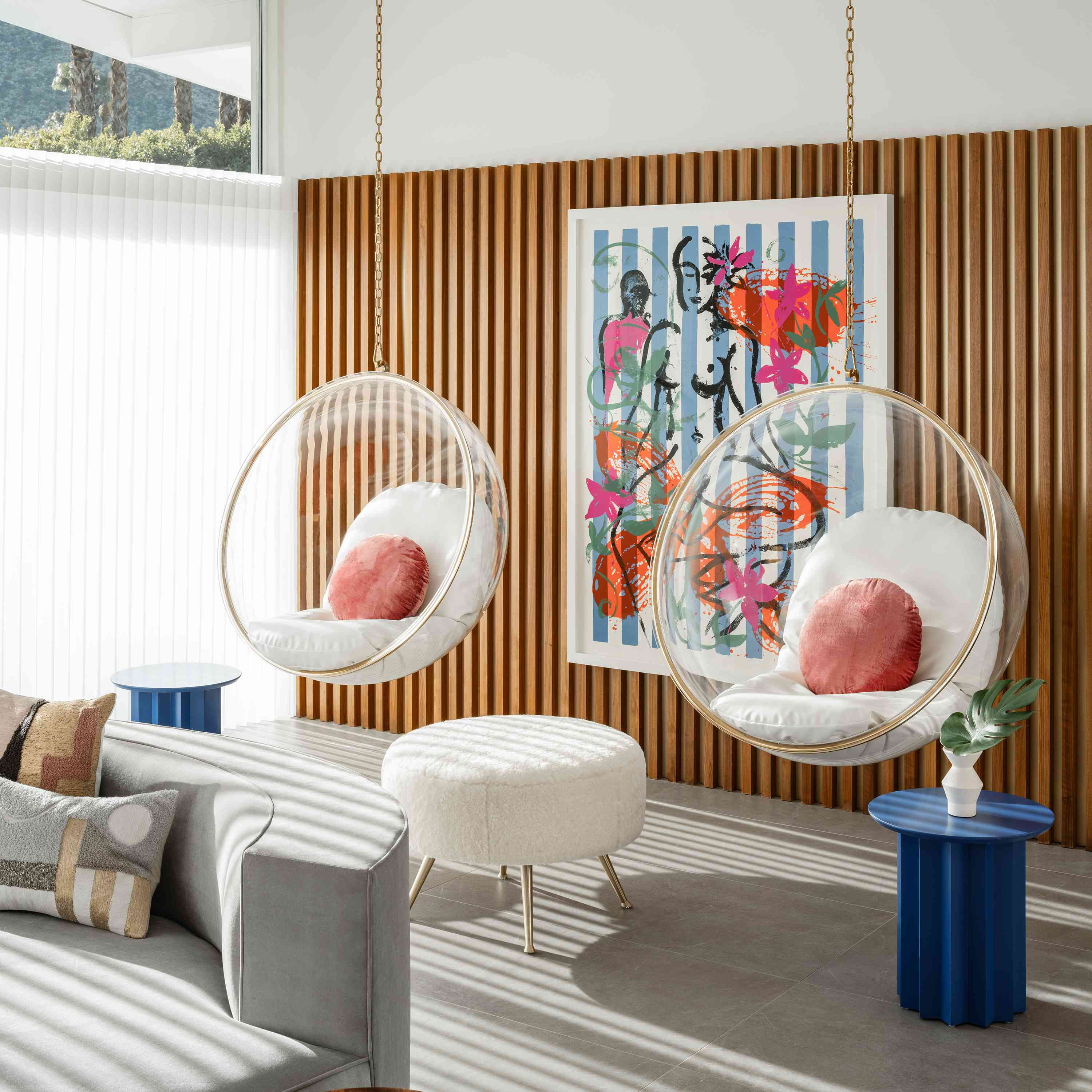 Two hanging bubble chairs in living room.