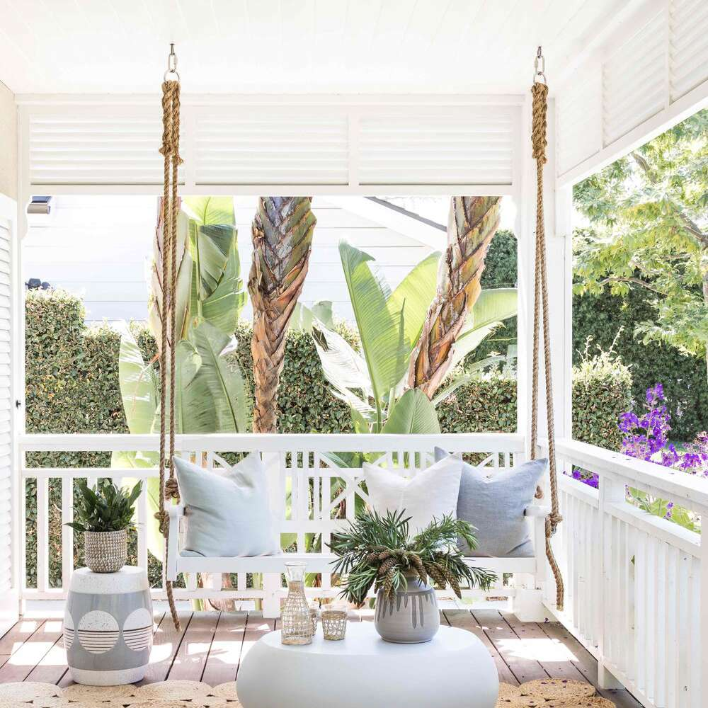 A deck outfitted with a rug, a porch swing, and a small table