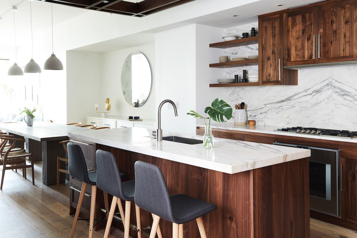 A kitchen with dark wooden cabinets and a bold marble backsplash
