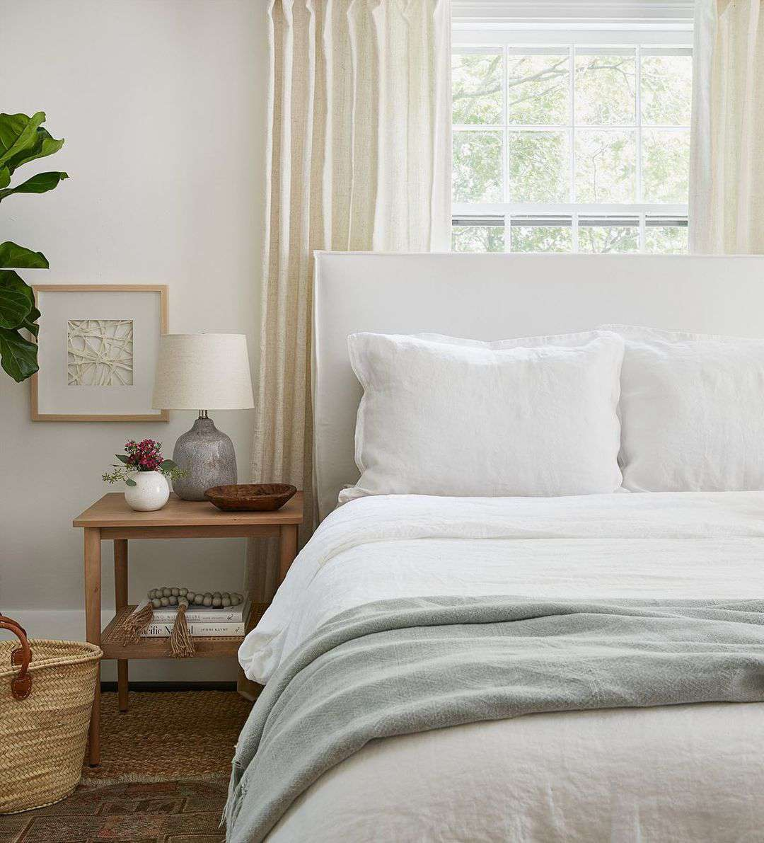Soft neutral bedroom with sun coming through the window.