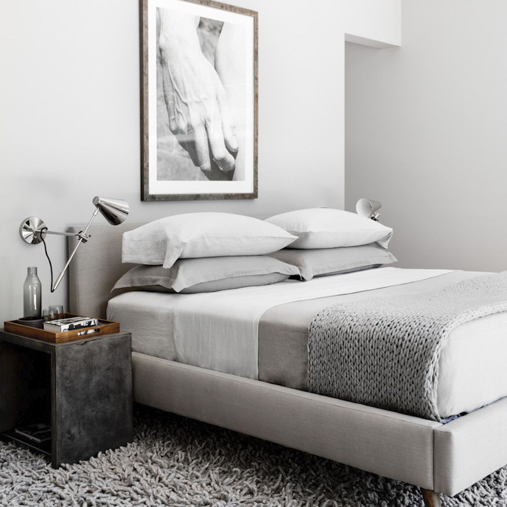 A light gray bedroom with a slate gray bedside table