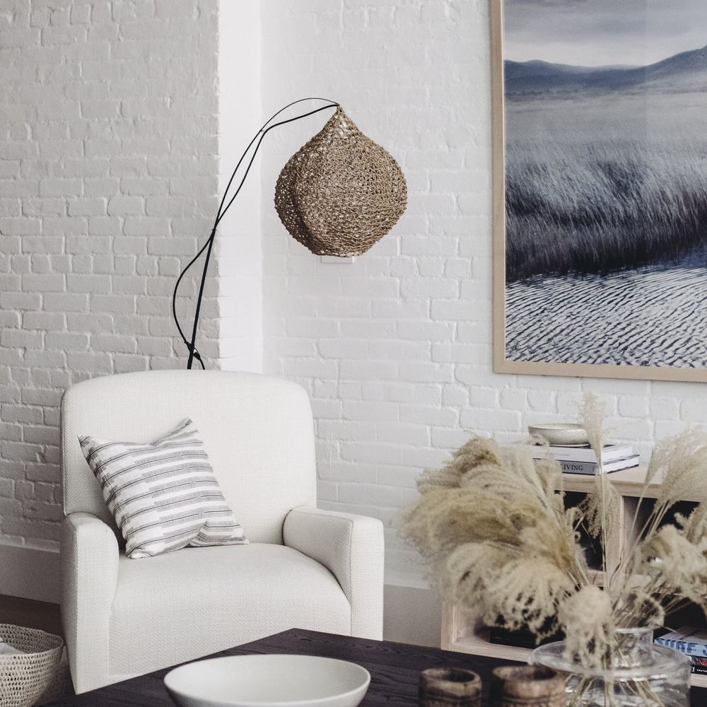 Living room with painted white brick walls, white accent chair, dark wood coffee table