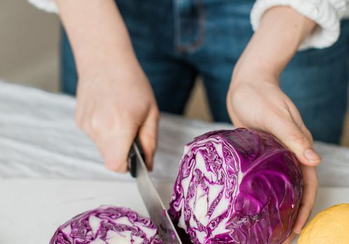 woman chopping red cabbage