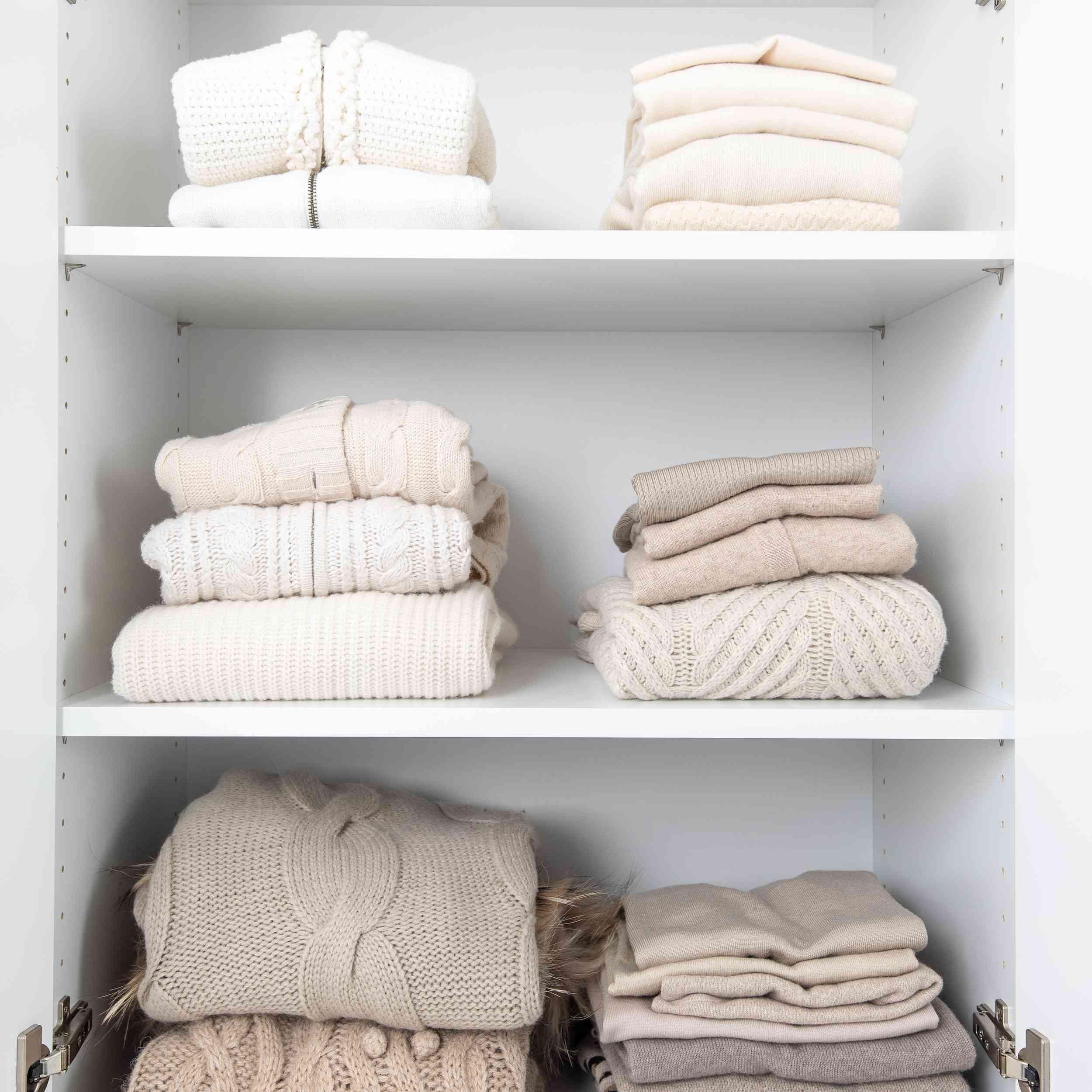 Folded sweaters in a closet