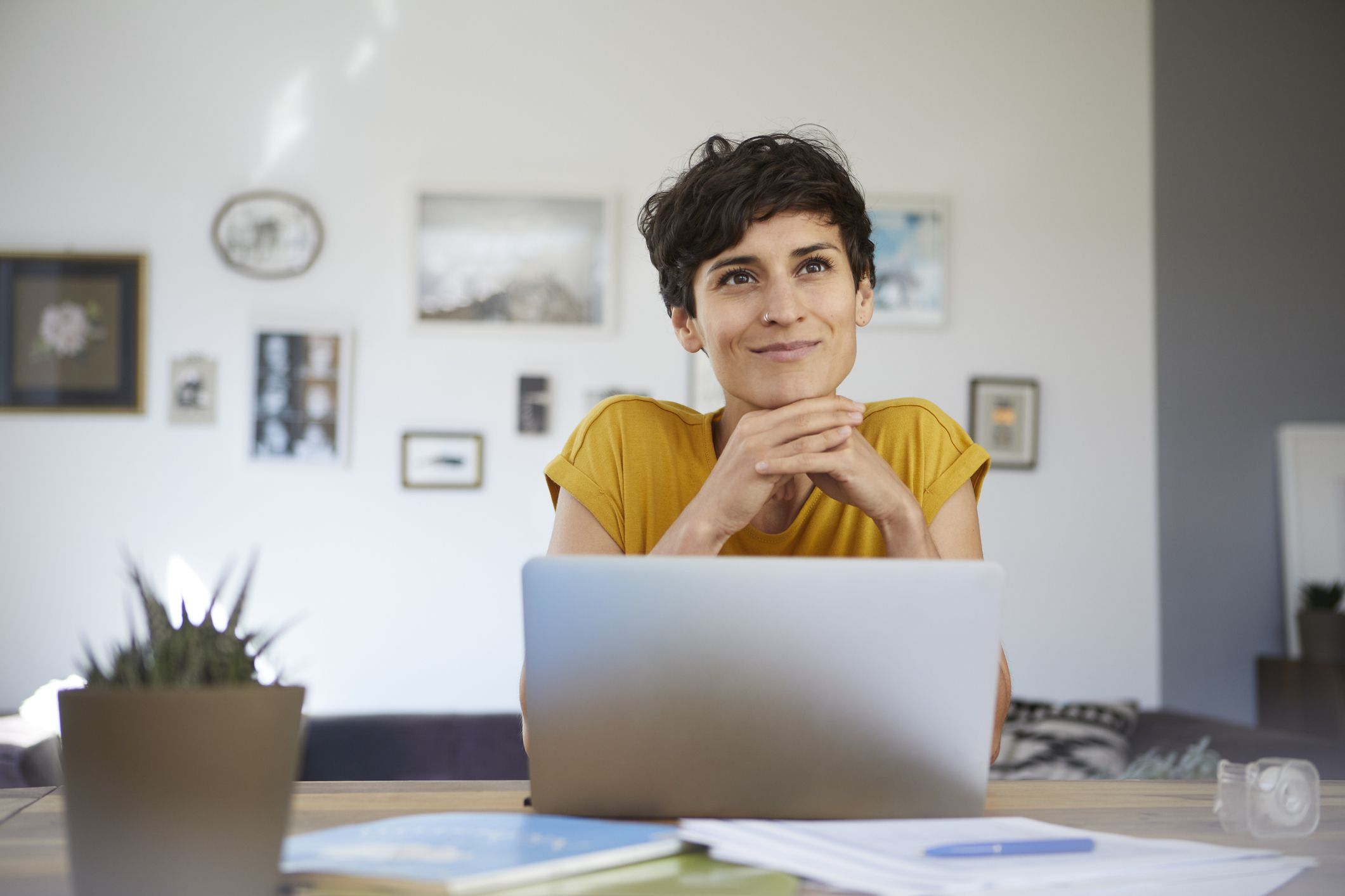 Woman sits in front of laptop, smiles into distance