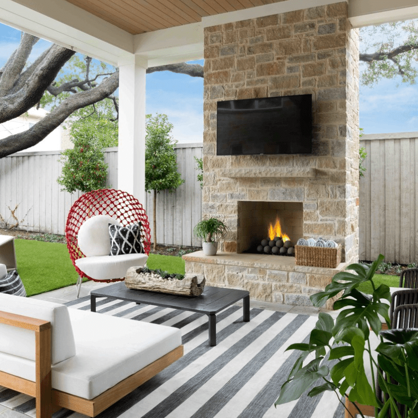 A covered patio decorated with an outdoor fireplace, a large TV, a striped rug, and plenty of cozy seating