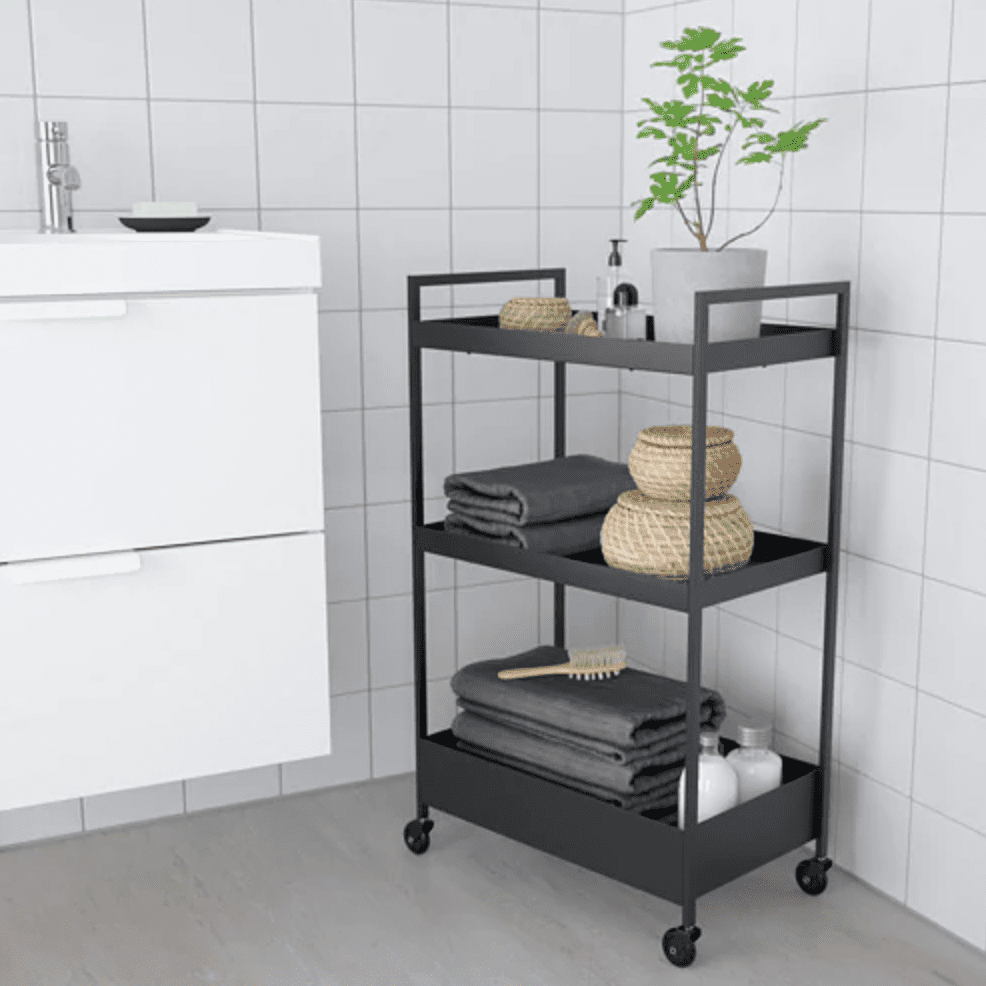 Small black bathroom cart with towels and plants on the shelves.