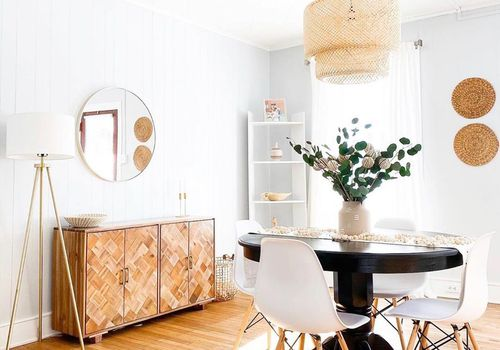 Bright boho dining room with natural fiber light fixture.