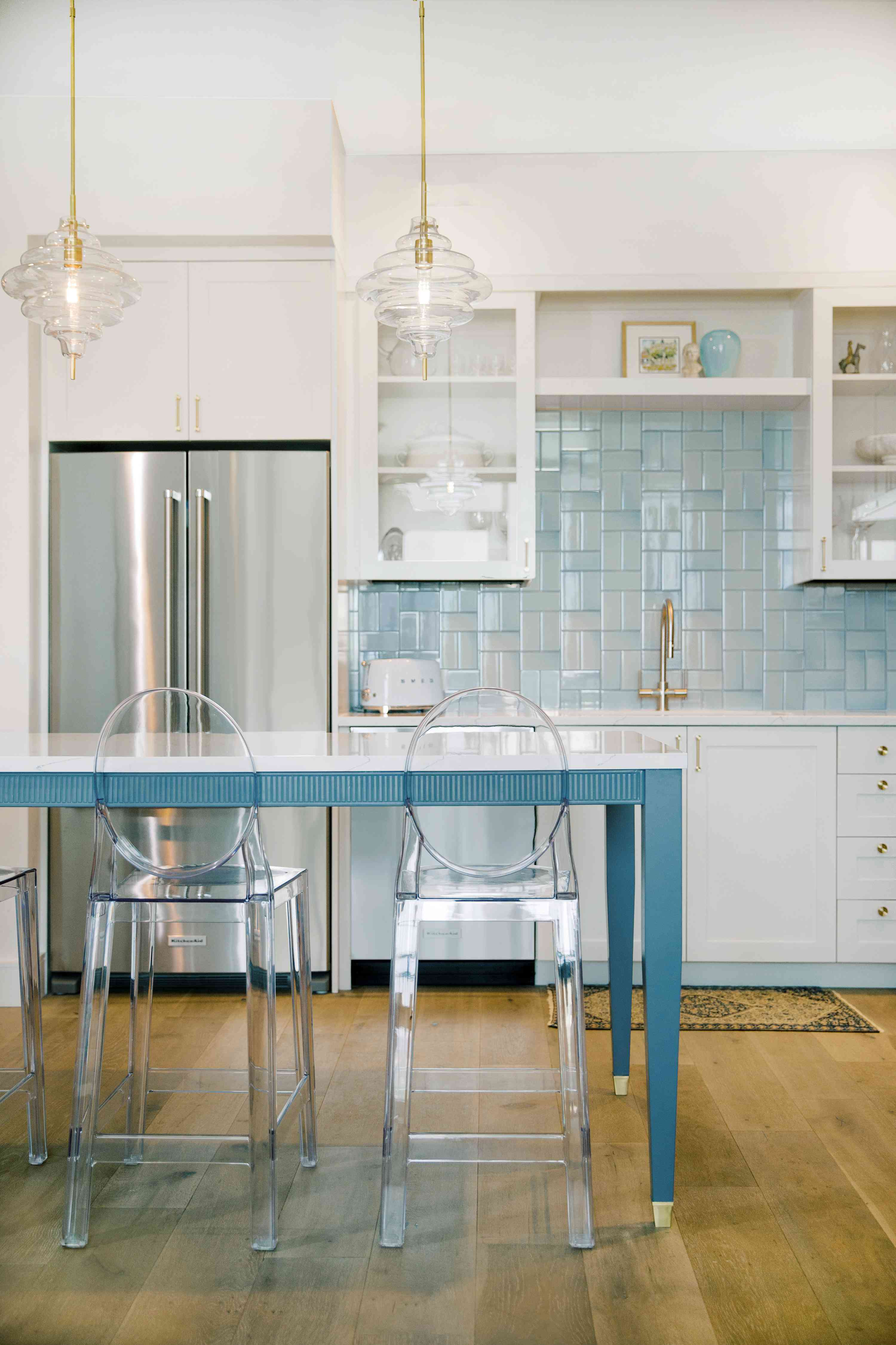Bright white kitchen with clear barstools.
