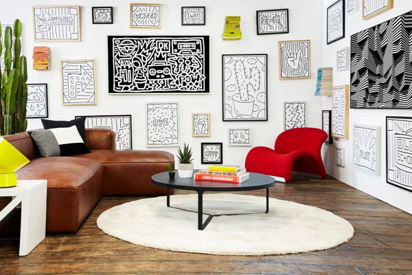 A living area with artwork hung salon-style on a gallery wall.