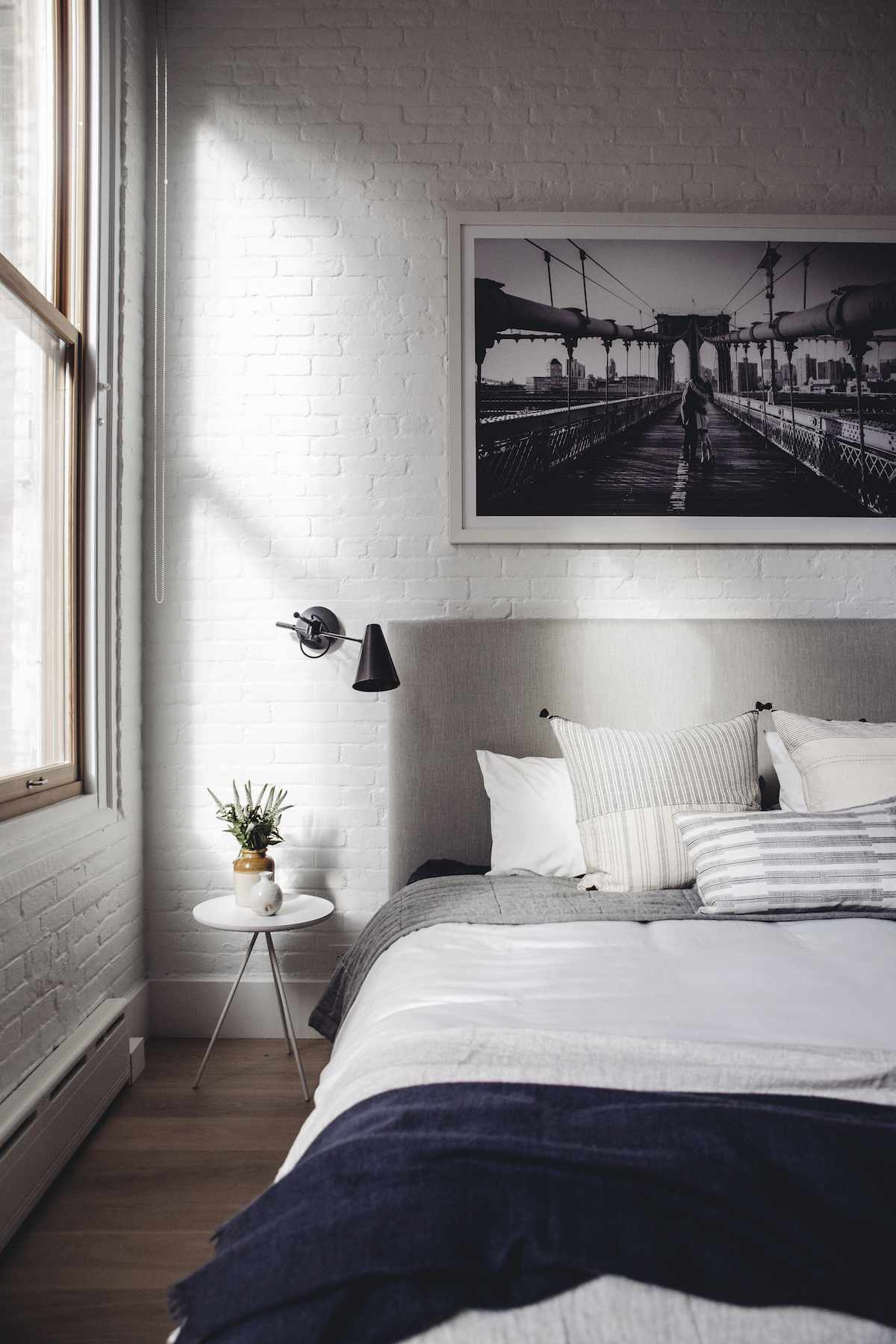 A bedroom with exposed brick walls that have been painted white