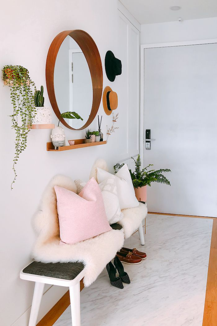 entryway with mirror, floating shelve, and bench with decorative pillows and furry throw