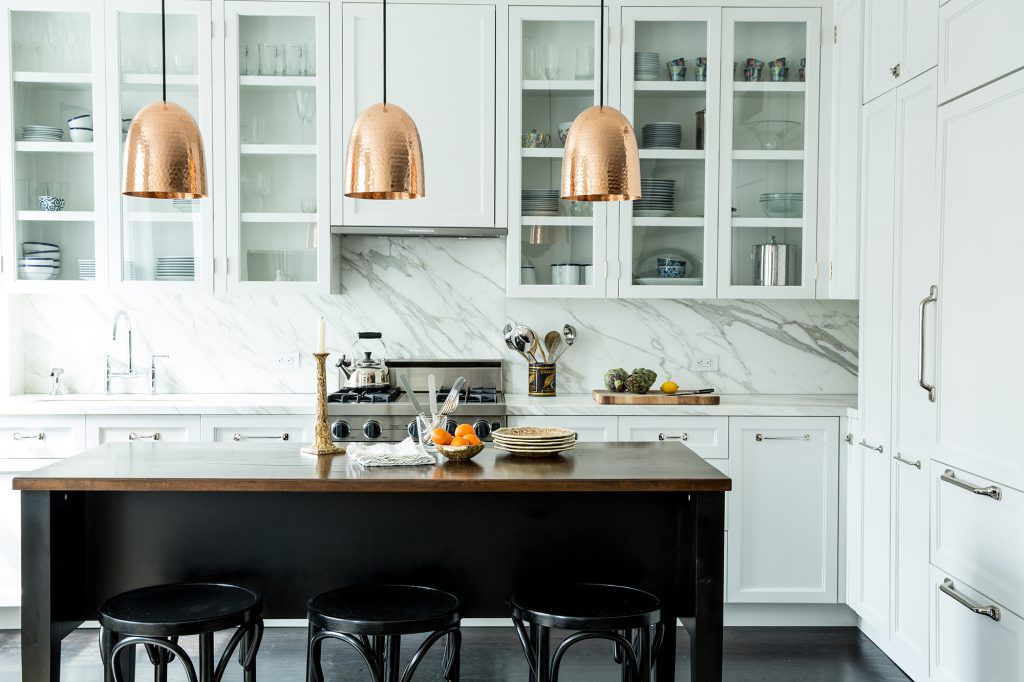 A white kitchen with vibrant copper lighting